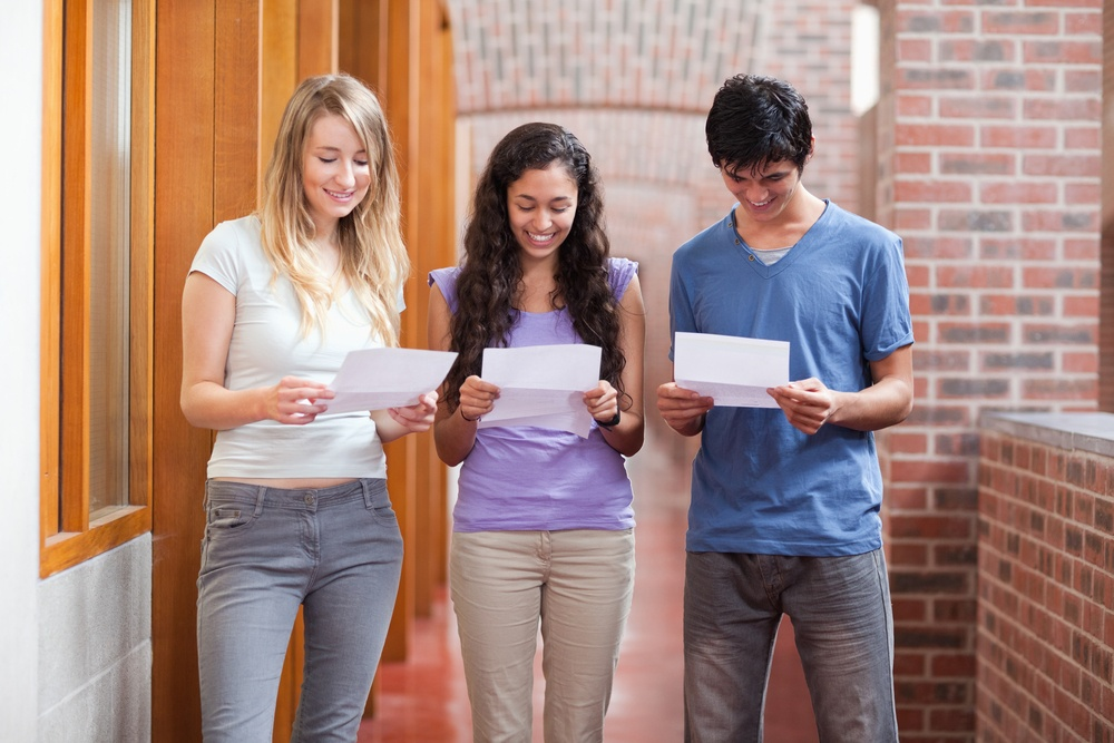 Students reading a piece of paper in a corridor.jpeg
