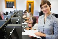 Teacher standing at the computer room holding papers in college.jpeg