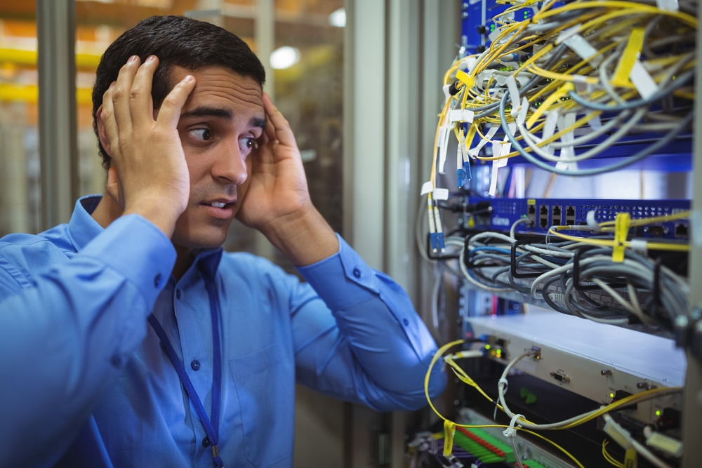 Technician getting stressed over server maintenance in server room.jpeg